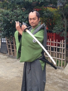 A shamed samurai actor posing for photos in a Kyoto film studio