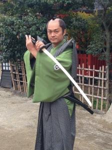 A shamed samurai actor posing for photos in a Kyoto film studio